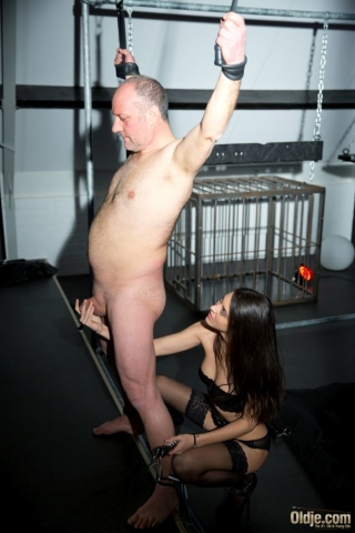 Naughty young girl plays with an old man's cock while he is tied up in ropes